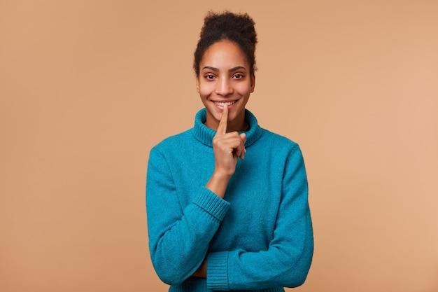 Młoda uśmiechnięta afroamerykanka o kręconych ciemnych włosach demonstruje gest ciszy, trzymając palec wskazujący przy ustach, wzywa do zachowania prywatności, sekretu, ciszy, spokoju.