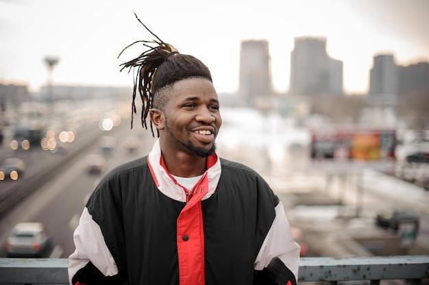 Młoda uśmiechnięta afroamerykańska mężczyzna pozycja na mieście