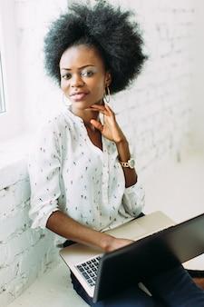 Młoda uśmiechnięta amerykanin afrykańskiego pochodzenia biznesowa kobieta używa laptop, siedzi na podłoga