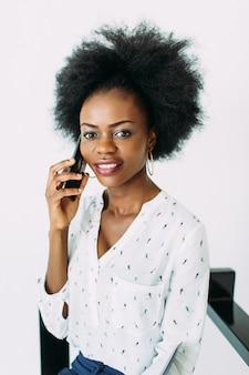 Młoda uśmiechnięta amerykanin afrykańskiego pochodzenia biznesowa kobieta używa telefon