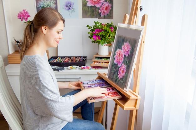 Młoda uśmiechnięta artystka kaukaski piękna dziewczyna maluje obraz z różowymi piwoniami za pomocą suchych pastelowych kredek w drewnianym pudełku. koncepcja kreatywności i hobby domowego