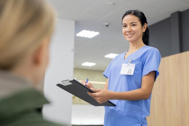 Młoda uśmiechnięta asystentka w niebieskim mundurze robi notatki w dokumencie rejestracyjnym, patrząc na jednego z pacjentów klinik stomatologicznych