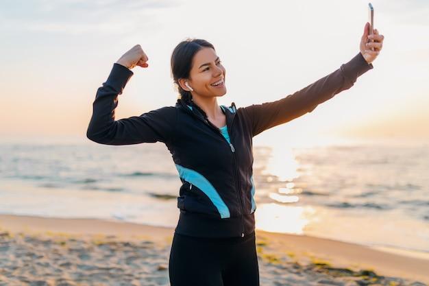 Młoda uśmiechnięta atrakcyjna szczupła kobieta robi ćwiczenia sportowe na plaży o poranku wschód słońca w strojach sportowych, zdrowy styl życia, słuchanie muzyki na słuchawkach, robienie zdjęć selfie na telefonie wyglądającym silnie