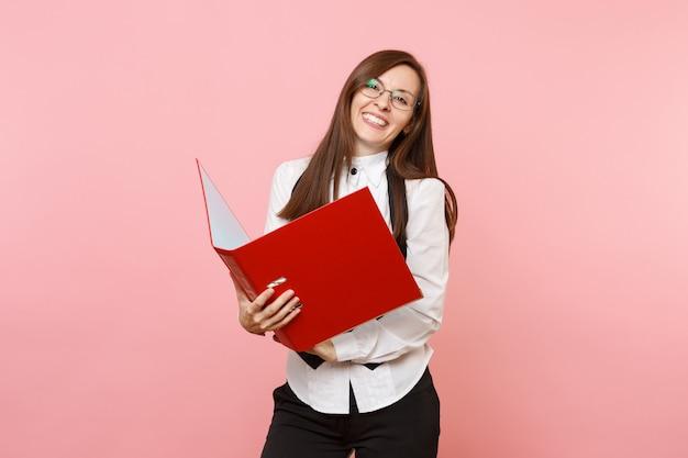 Młoda uśmiechnięta atrakcyjna udanego biznesu kobieta w okularach trzyma czerwony folder na dokument dokumentów na białym tle na różowym tle. szefowa. osiągnięcie bogactwa kariery. skopiuj miejsce na reklamę.