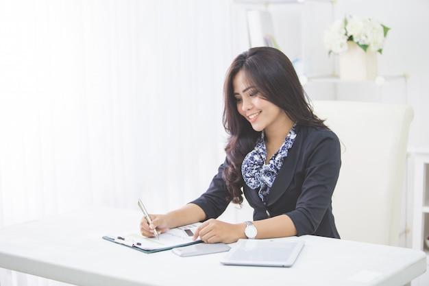 Młoda uśmiechnięta biznesowa kobieta pracuje na jej papierkowej robocie