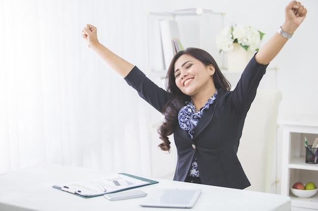 Młoda uśmiechnięta biznesowej kobiety podwyżki ręka po kończyć jej pracę