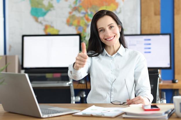 Młoda uśmiechnięta bizneswoman pokazując kciuk do góry gest siedząc przy stole roboczym w biurze