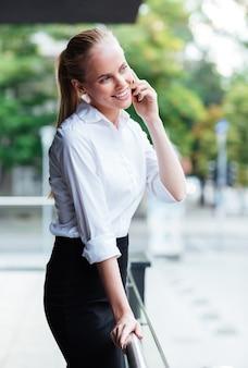 Młoda uśmiechnięta bizneswoman rozmawia przez telefon komórkowy na zewnątrz