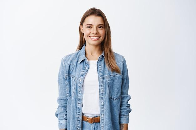 Młoda uśmiechnięta blond dziewczyna z idealnymi zębami, patrząca z przodu, stojąca zrelaksowana przy białej ścianie w codziennych ubraniach, koncepcji stylu życia i emocji