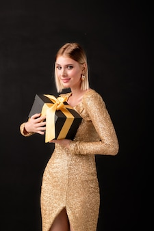 Młoda uśmiechnięta blond kobieta w eleganckiej sukience patrząc na ciebie, trzymając czarne pudełko zawierające urodzinową niespodziankę dla niej
