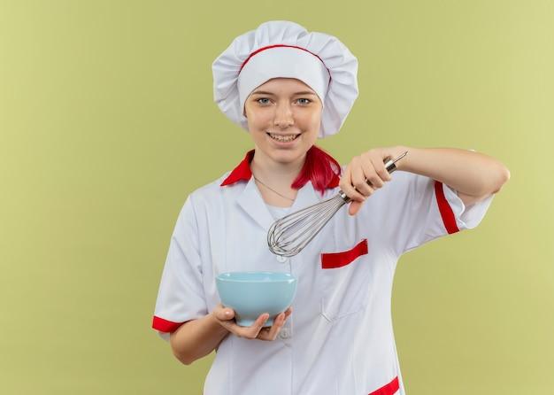 Młoda uśmiechnięta blondynka kobieta szefa kuchni w mundurze szefa kuchni trzyma miskę i trzepaczkę na białym tle na zielonej ścianie