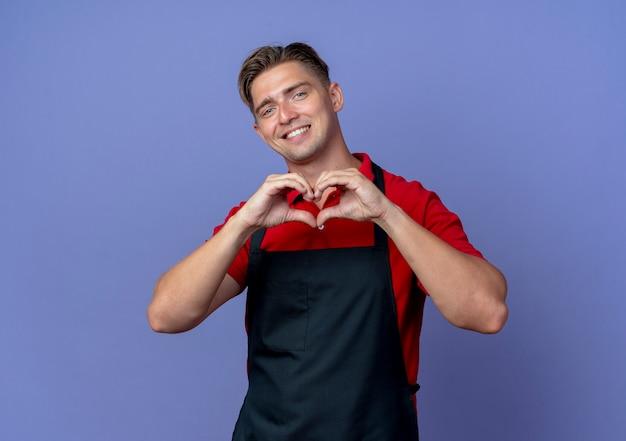 Młoda uśmiechnięta blondynka mężczyzna fryzjer w mundurze gestów serce znak ręką na białym tle na fioletowej przestrzeni z miejsca na kopię