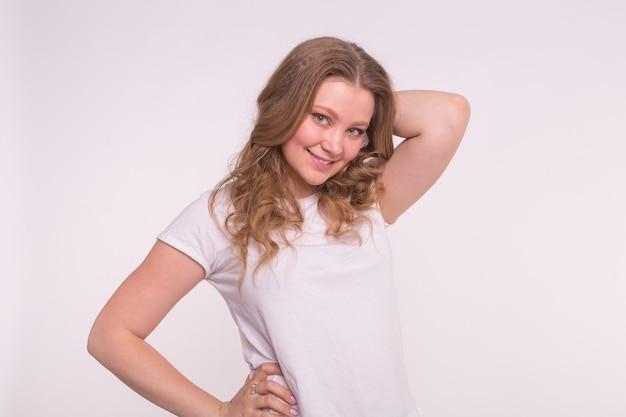 Młoda uśmiechnięta blondynka pozowanie na białym tle