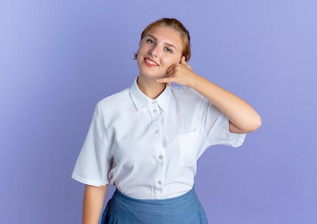 Młoda uśmiechnięta blondynka rosjanka gesty zadzwoń do mnie znak na białym tle na fioletowym tle z miejsca na kopię