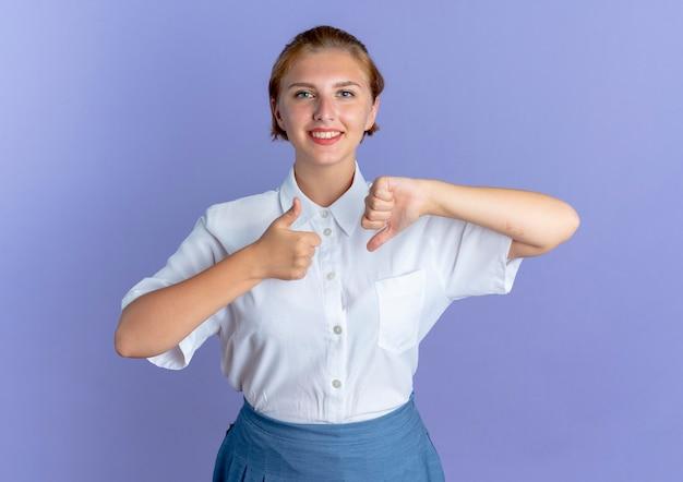 Młoda uśmiechnięta blondynka rosjanka kciuki w górę i w dół na białym tle na fioletowym tle z miejsca na kopię