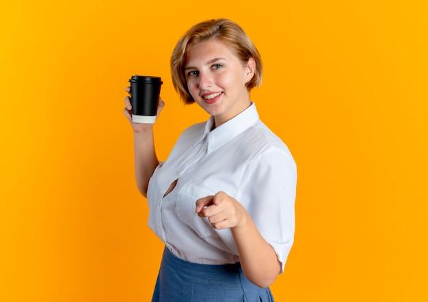 Młoda uśmiechnięta blondynka rosjanka stoi bokiem trzymając filiżankę kawy i wskazując na aparat
