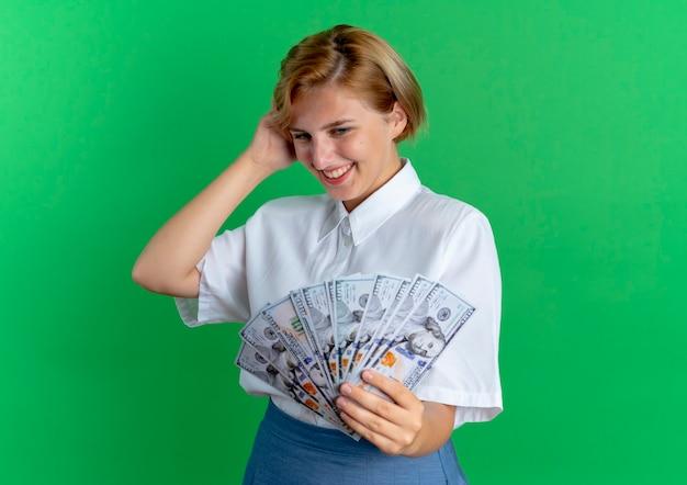 Młoda uśmiechnięta blondynka rosjanka trzyma i patrzy na pieniądze kładzie rękę na głowie na białym tle na zielonym tle z miejsca kopiowania