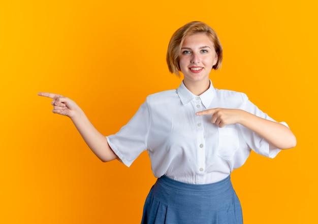 Młoda uśmiechnięta blondynka rosjanka wskazuje dwiema rękami z boku patrząc na kamery
