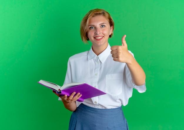 Młoda uśmiechnięta blondynka rosyjski kciuki do góry trzymając książkę na białym tle na zielonym tle z miejsca kopiowania