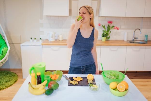 Młoda uśmiechnięta blondynki kobieta gryźć organicznie jabłka podczas gdy gotujący świeże owoc w kuchni