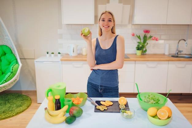 Młoda uśmiechnięta blondynki kobieta trzyma gryźć zielonego jabłka podczas gdy gotujący świeże owoc w kuchni.