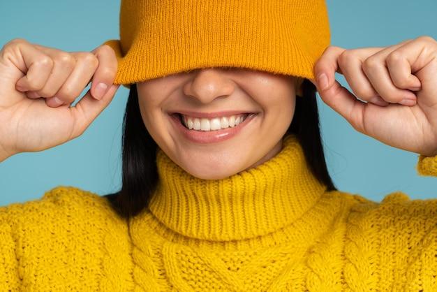 Młoda uśmiechnięta brunetka kobieta ubrana w biały sweter z dzianiny i kapelusz pozowanie na tle niebieski studio na białym tle. koncepcja ciepłego zimowego sezonu zimowego