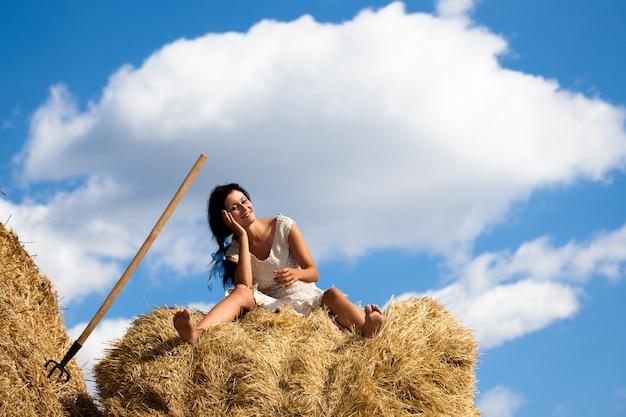Młoda uśmiechnięta brunetka kobieta w białej sukni siedzi na stosie siana