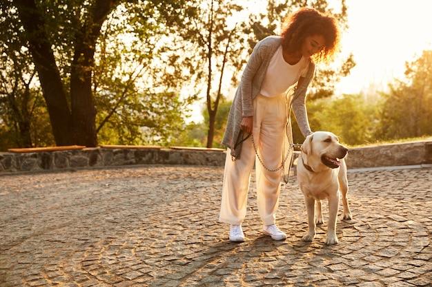 Młoda uśmiechnięta dama w przypadkowych ubraniach siedzi psa i ściska w parku