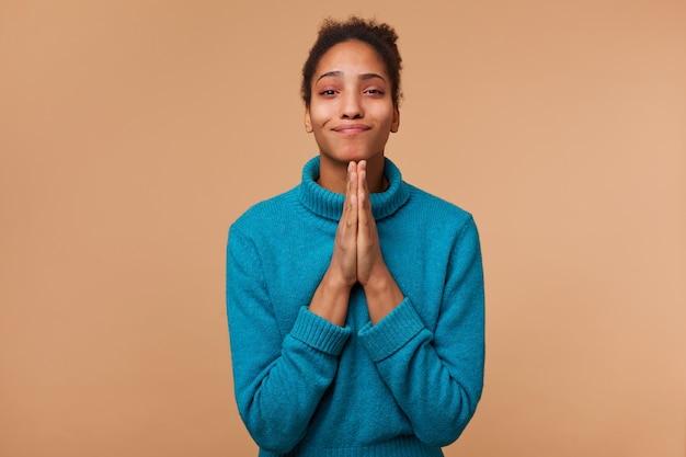Młoda uśmiechnięta dziewczyna african american z kręconymi ciemnymi włosami ubrana w niebieski sweter. uśmiecha się, trzyma dłonie razem, prosi, błaga o litość. na białym tle nad biege tle.