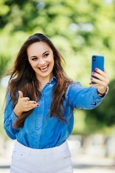 Młoda uśmiechnięta dziewczyna co selfie macha na aparat lub nawiązać połączenie wideo na tle miasta