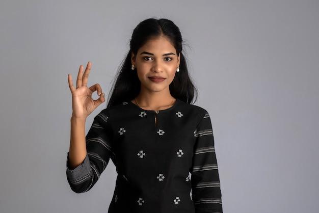 Młoda uśmiechnięta dziewczyna pokazuje znak ok lub kciuki do góry na szarym tle