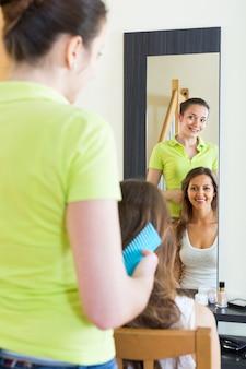 Młoda uśmiechnięta dziewczyna robi fryzurze