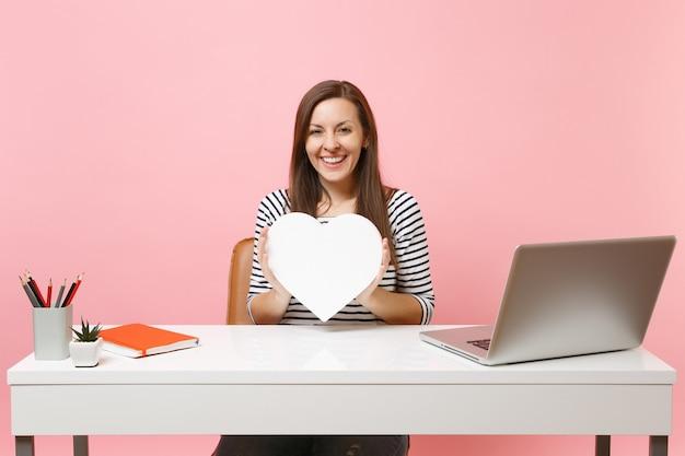 Młoda uśmiechnięta dziewczyna trzyma białe serce z kopią przestrzeni, pracując nad projektem, siedząc w biurze z laptopem