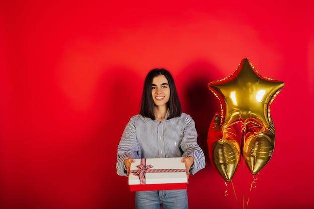 Młoda uśmiechnięta dziewczyna trzyma duże czerwone pudełko z okazji urodzin na czerwonej powierzchni z miejsca na kopię.