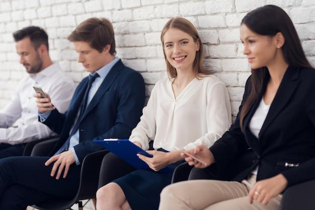Młoda uśmiechnięta dziewczyna w błękitnym kostiumu siedzi w poczekalni.