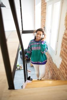 Młoda, uśmiechnięta dziewczyna wchodząca po schodach wewnątrz swojego domu. ona ma na sobie słuchawki. miejsce na tekst.