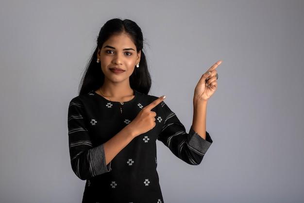 Młoda uśmiechnięta dziewczyna wskazując palcami, aby skopiować miejsce na szarym tle