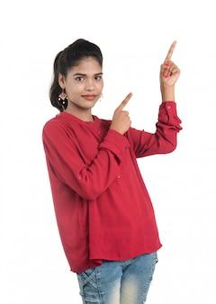 Młoda uśmiechnięta dziewczyna wskazuje palce kopiować przestrzeń na białej przestrzeni