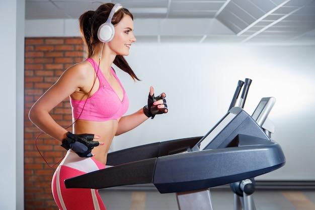 Młoda uśmiechnięta dziewczyna z hełmofonami biega na bieżni w klubie sportowym.