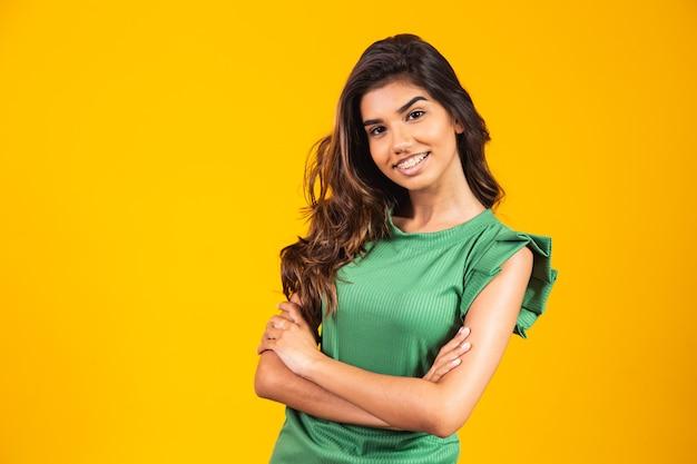 Młoda uśmiechnięta dziewczyna z rękami skrzyżowanymi na żółtym tle.