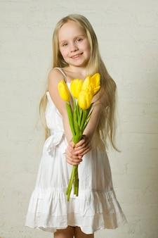 Młoda uśmiechnięta dziewczyna z żółtymi kwiatami