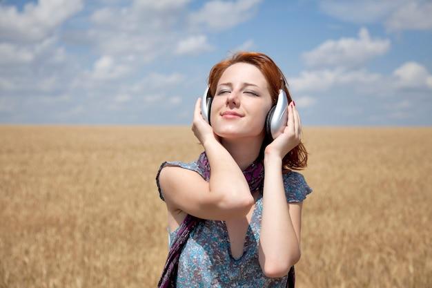 Młoda uśmiechnięta dziewczyna ze słuchawkami w polu pszenicy.