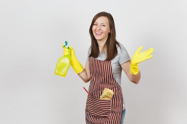 Młoda uśmiechnięta gospodyni domowa w żółtych rękawiczkach, pasiasty fartuch, szmata do czyszczenia, ściągaczka w kieszeni na białym tle