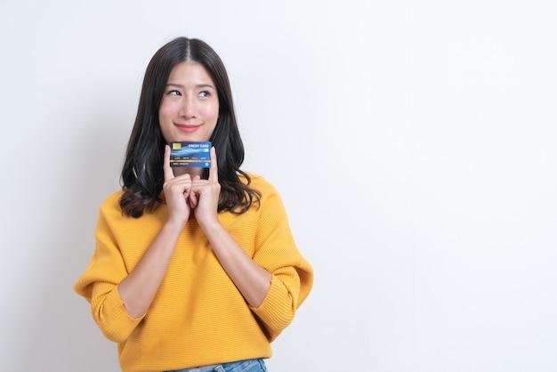 Młoda uśmiechnięta i piękna azjatka przedstawia w ręku kartę kredytową, pokazując zaufanie i pewność przy dokonywaniu płatności