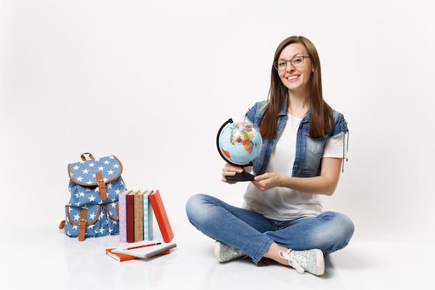 Młoda uśmiechnięta, inteligentna studentka w okularach trzymająca kulę ziemską, ucząca się geografii, siedząca w pobliżu plecaka szkolnego podręcznika na białym tle