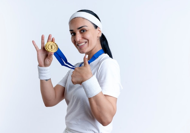 Młoda uśmiechnięta kaukaski kobieta sportowa na sobie opaskę i opaski na rękę posiada złoty medal i kciuki do góry na białym tle na białej przestrzeni z miejsca na kopię