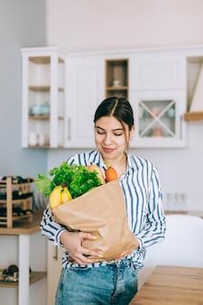 Młoda uśmiechnięta kaukaski kobieta trzyma ekologiczną torbę na zakupy ze świeżymi warzywami i bagietką w nowoczesnej kuchni.