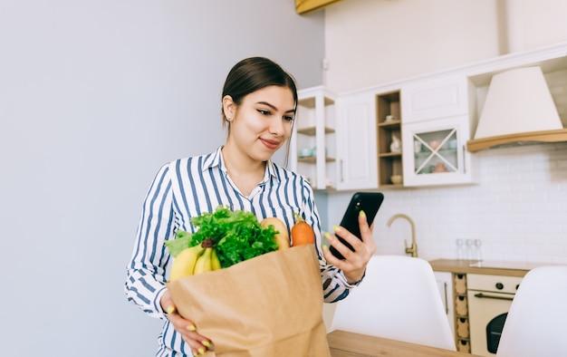 Młoda uśmiechnięta kaukaski kobieta używa smartfona w nowoczesnej kuchni, worek ze świeżymi warzywami na stole. kupowanie żywności i artykułów spożywczych przez internet.
