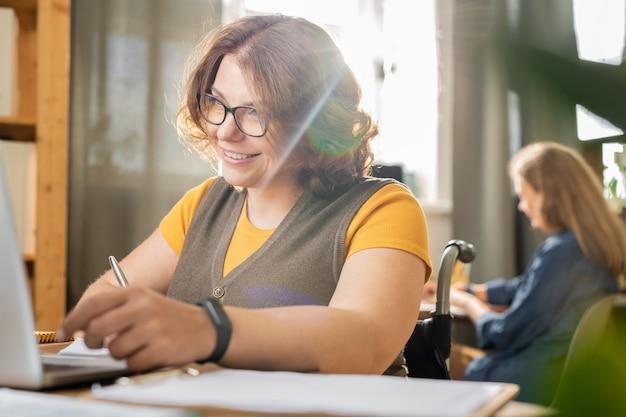 Młoda uśmiechnięta kierownik biura niepełnosprawnego w stroju casual, siedząca na wózku inwalidzkim i patrząca na wyświetlacz laptopa, podczas gdy jej kolega pracuje z tyłu
