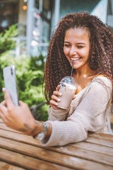 Młoda uśmiechnięta kobieta afro włosach wziąć selfie z białym smartphone siedząc w kawiarni na zewnątrz w słoneczny letni dzień.